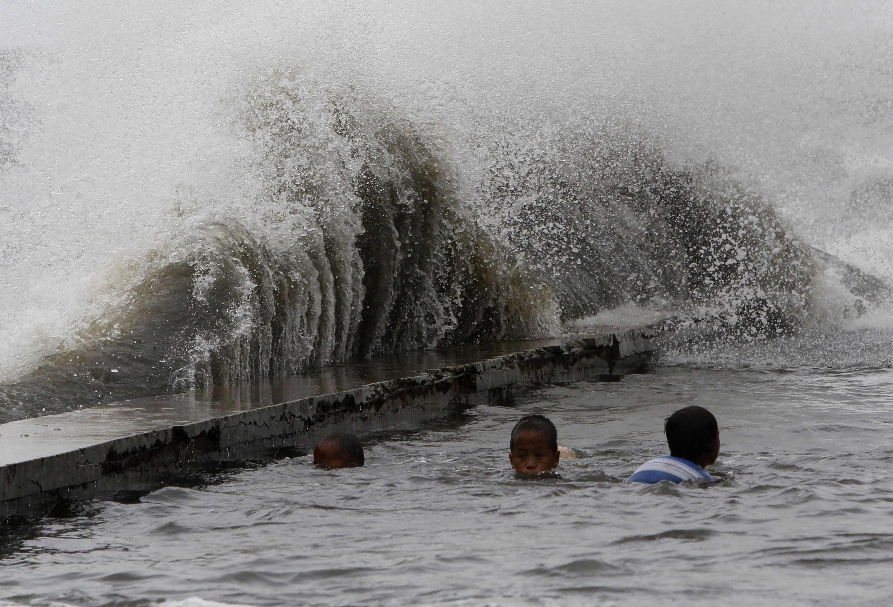 Duas crianças nadam numa das ruas que ficou inundada em Manila, nas Filipinas